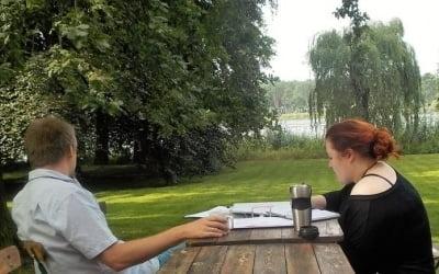 Außenanlage Villa Fohrde mit Blick auf Havel. Zwei Personen an Tisch.