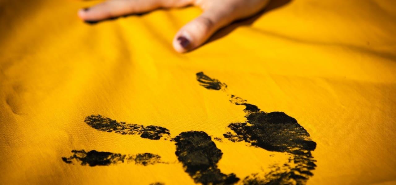Handabdruck (schwarz) auf gelben Transparent für Campact-Aktion gegen Kohle.